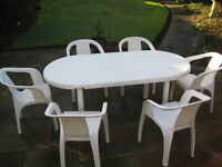 Large oval garden table and 6 chairs - white plastic. Table has some wear. Chairs in good condition