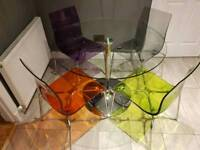 Round glass dining table and four gel style chairs.