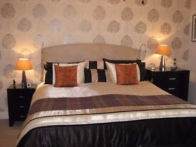 Black high gloss mirrored chests of drawers, upholstered chaise longue, mirror & chandelier fitting.