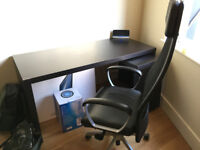 Black-brown wooden desk with pull out panel and office chair