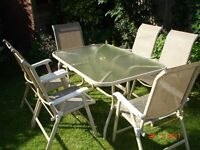 Glass top patio table and 6 folding chairs.