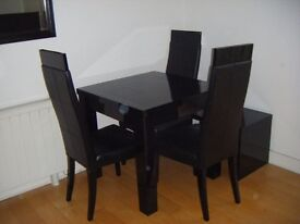Black high gloss dining table with three leather chairs and nesting table of 3 pieces.
