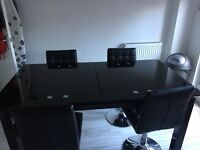 Dinning table and chairs (4) extendable glass in black with 4 leather chairs in fair condition