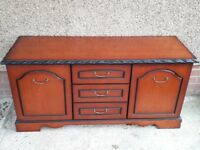 Dark stained varnished wooden side unit with 3 middle drawers & cupboard with shelf on either side.