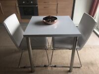 Fold out white and chrome dining table and two chairs