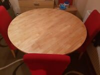 ROUND DINING TABLE AND FOUR RED UPHOLSTERED CHAIRS