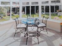 Round glass table with black metal base and 4 black metal chairs
