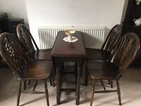 Drop leaf oak table and four wheel backed chairs.