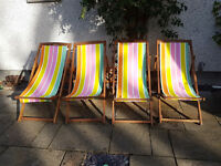 Set of four wooden deckchairs with striped covers