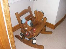 A cute wooden rocking chair with a carved teddy shape on each side.