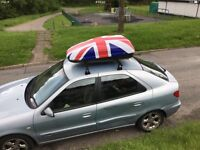 Roof box with lockable universal bars