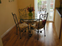 Attractive Glass top dining table and 4 chairs with padded cream seats
