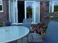 Aluminium glass topped table and four chairs.