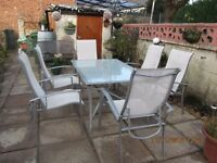large glass topped patio table with 6 adjustable armchairs