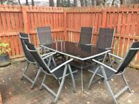 Glass topped garden dining table with 6 chairs and parasol