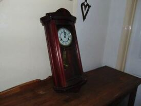 large wall clock with pendulum and key mechanism