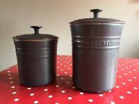 Two Le Creuset kitchen storage pots with lids