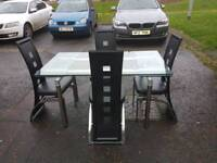 Glass extendable table and 4 black leather chairs