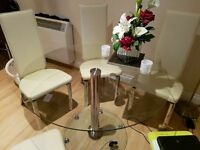 round glass table and 4 cream chairs