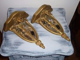 A pair of mirrored matching wall plaques in a gold finish.