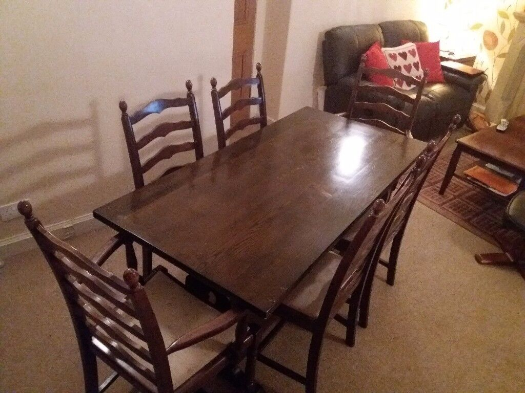 Solid Wood traditional table, 2 carver chairs and 4 other chairs. Dark Brown with cream seats.