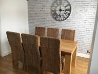 Solid oak dining table with 6 wicker chairs.
