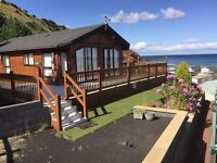 Luxury lodge for sale with conservatory, hot tub and large decking with stunning sea views.