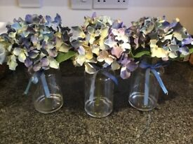 Three blue flowers in glass jars from next