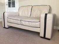 2 x 2 seater leather cream sofa with dark brown trim and footstool