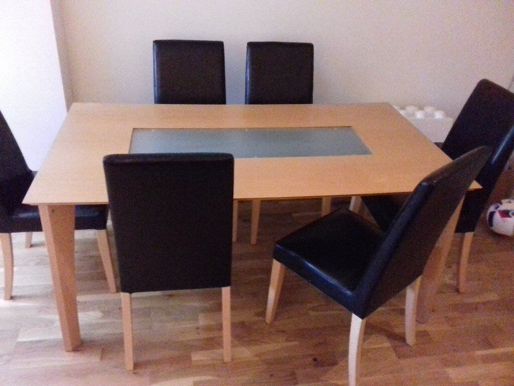 Lovely light wood with frosted glass insert table, with 6 black faux leather chairs.