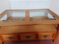 Solid wood coffee table with glass top. Three drawers with metal handles.
