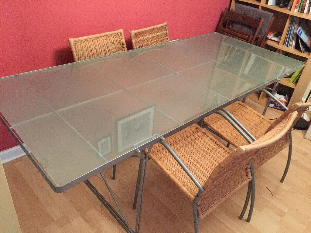 Glass dining table and four wicker chairs