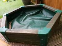 Handmade, wooden sandpit with rain cover.