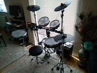 TRAPS ELECTRIC DRUM KIT COMPLETE WITH HEADPHONES, AMPLIFIER, STOOL AND DRUMSTICKS.