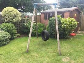 Tyre swing on a wooden frame .