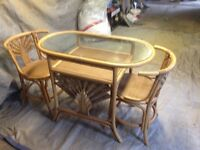 Wicker breakfast table and two chairs which fit under