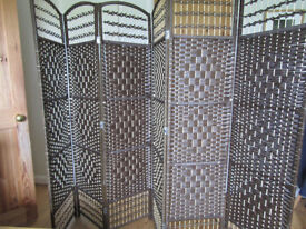 Brown and cream natural rattan screen, with folding panels.