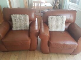 Two tan leather armchairs. Like new condition. One small mark as shown in picture. 12 months old.