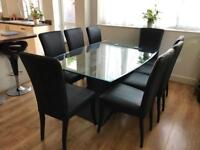Gorgeous glass table from Harvey's plus 8 black leather chairs