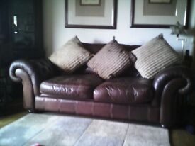 Large chocolate brown leather chesterfield style sofa perfect for lounging or entertaining