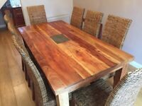 Solid Acacia wood Dining table and eight Rattan chairs. Good condition. Collection only