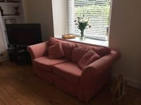 2 seater sofa for sale - salmon covers and ivory change covers. Good condition. £100 ono