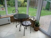 Bistro granite top table in black with two chairs and cushions.