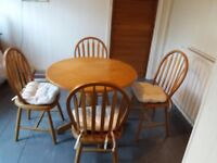 round solid wood dinning table and four chairs.