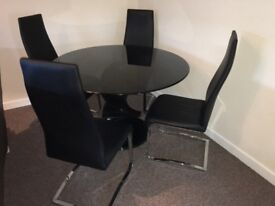 Barker and Stonehouse round glass dining table with 4 black high backed chairs