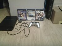 Playstation 2 with games and a controller