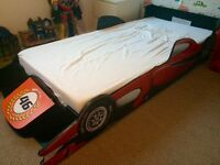 Single red race car bed with small storage. No mattress