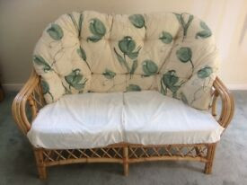 Set of cane furniture featuring 2 seater sofa and two chairs.