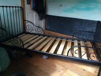 Black metal Ikea Minnen extendable bed frame with slatted base