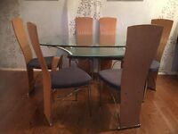 Glass top dining table & 6 matching padded grey chairs.